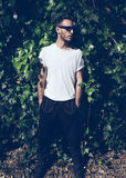 Homem novo farpado do retrato com a tatuagem que veste o tshirt branco vazio e óculos de sol pretos Fundo verde da parede do jard imagens de stock