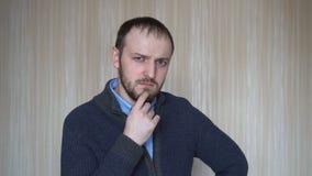 Homem novo farpado duvidoso que olha com os suspeitos do homem da desconfiança alguém filme