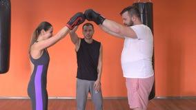 Homem novo farpado e encaixotamento caucasiano do boxe de treino da menina no gym sob a supervisão de um instrutor filme
