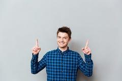 Homem novo feliz atrativo que está sobre a parede cinzenta e apontar imagem de stock