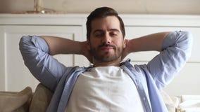 Homem novo feliz calmo que relaxa com os olhos fechados no sofá vídeos de arquivo