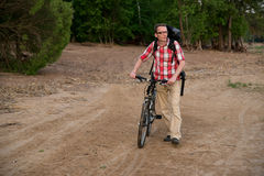 Homem novo feliz com a bicicleta, andando na praia Fotografia de Stock Royalty Free
