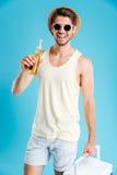 Homem novo feliz com cerveja estando e bebendo mais fresca do saco Imagem de Stock