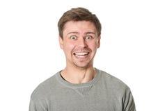 Homem novo feliz com expressão maníaca, no fundo cinzento Imagem de Stock