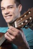 Homem novo feliz com guitarra Imagem de Stock
