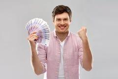 Homem novo feliz com o fã do euro- dinheiro imagens de stock royalty free