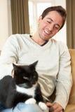 Homem novo feliz com o gato que senta-se no sofá Imagens de Stock