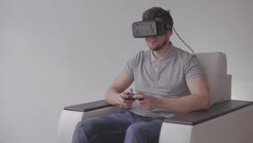 Homem novo feliz com os auriculares da realidade virtual ou os vidros 3d com controlador Gamepad Playing que compete o jogo de ví vídeos de arquivo