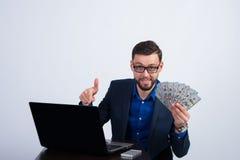 Homem novo feliz com salário no Internet Fotografia de Stock Royalty Free