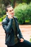 Homem novo feliz com smartphone Fala no telefone Fotografia de Stock Royalty Free