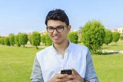 Homem novo feliz com telefone móvel Fotografia de Stock Royalty Free