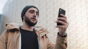 Homem novo feliz da barba que tem a câmara web video do smartphone da terra arrendada do bate-papo que conversa com amigos fora video estoque