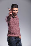 Homem novo feliz da forma que mostra o sinal da vitória Fotos de Stock Royalty Free
