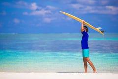 Homem novo feliz da ressaca na praia branca com amarelo Imagem de Stock