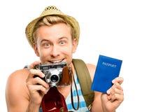 Homem novo feliz do turista que mantem o branco retro da câmera do passaporte traseiro Fotografia de Stock