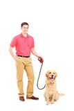 Homem novo feliz e um cão em uma trela Imagem de Stock