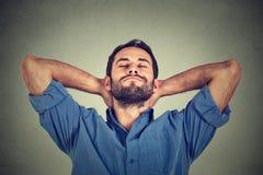 Homem novo feliz na camisa azul que olha para cima no relaxamento ou na dormida do pensamento fotografia de stock royalty free