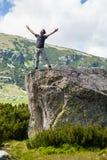Homem novo feliz nas montanhas Fotos de Stock