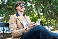Homem novo feliz no parque usando Smartphone imagens de stock