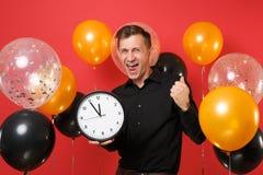 Homem novo feliz no punho de aperto clássico preto da camisa como o vencedor, guardando o pulso de disparo redondo em balões de a imagens de stock royalty free