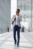 Homem novo feliz que anda e que fala no telefone celular Foto de Stock