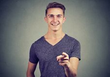 Homem novo feliz que aponta seu dedo em você foto de stock