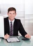 Homem novo feliz que calcula finanças Fotografia de Stock Royalty Free