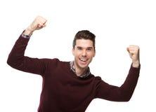 Homem novo feliz que cheering com os braços aumentados Imagem de Stock