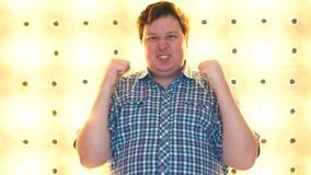 Homem novo feliz que comemora seu sucesso sobre brilhantemente o fundo filme