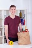 Homem novo feliz que desembala mantimentos na cozinha imagens de stock