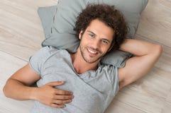 Homem novo feliz que encontra-se no assoalho Fotografia de Stock Royalty Free