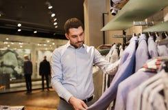 Homem novo feliz que escolhe a roupa na loja de roupa Foto de Stock