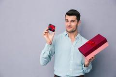 Homem novo feliz que guarda a caixa de presente pequena e grande Fotografia de Stock