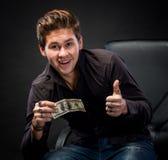Homem novo feliz que guarda o dinheiro Fotografia de Stock