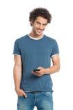 Homem novo feliz que guarda o telefone celular Imagem de Stock