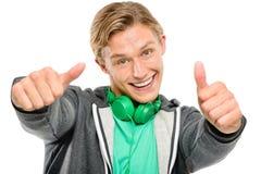 Homem novo feliz que mantem o sorriso dos polegares acima isolado na parte traseira do branco foto de stock royalty free