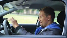 Homem novo feliz que obtém suas chaves no carro vídeos de arquivo