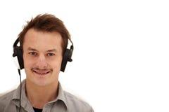 Homem novo feliz que olha o e que escuta Imagens de Stock