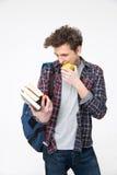 Homem novo feliz que olha o livro Imagens de Stock