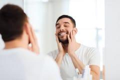 Homem novo feliz que olha para espelhar em casa o banheiro Imagens de Stock