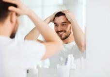 Homem novo feliz que olha para espelhar em casa o banheiro Fotografia de Stock Royalty Free