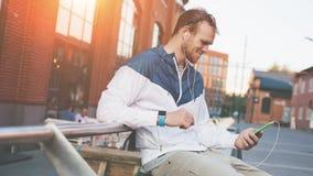 Homem novo feliz que olha seu telefone celular, sentando-se no banco fora foto de stock