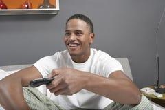 Homem novo feliz que olha a tevê imagem de stock