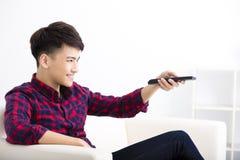 Homem novo feliz que olha a tevê no sofá Imagens de Stock
