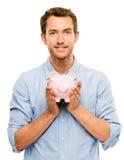Homem novo feliz que põe o dinheiro no mealheiro isolado no branco Foto de Stock