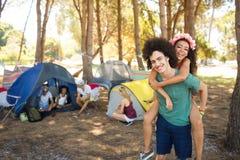Homem novo feliz que reboca a mulher com os amigos no fundo Imagens de Stock