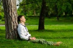 Homem novo feliz que relaxa no parque no dia de mola ensolarado Imagens de Stock Royalty Free