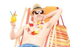 Homem novo feliz que senta-se em uma cadeira de praia e em um cocktail bebendo Imagem de Stock Royalty Free