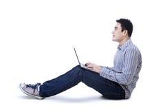 Homem novo feliz que senta-se no assoalho com portátil Foto de Stock