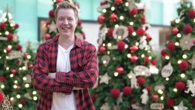 Homem novo feliz que sorri contra árvores de Natal iluminadas fora vídeos de arquivo